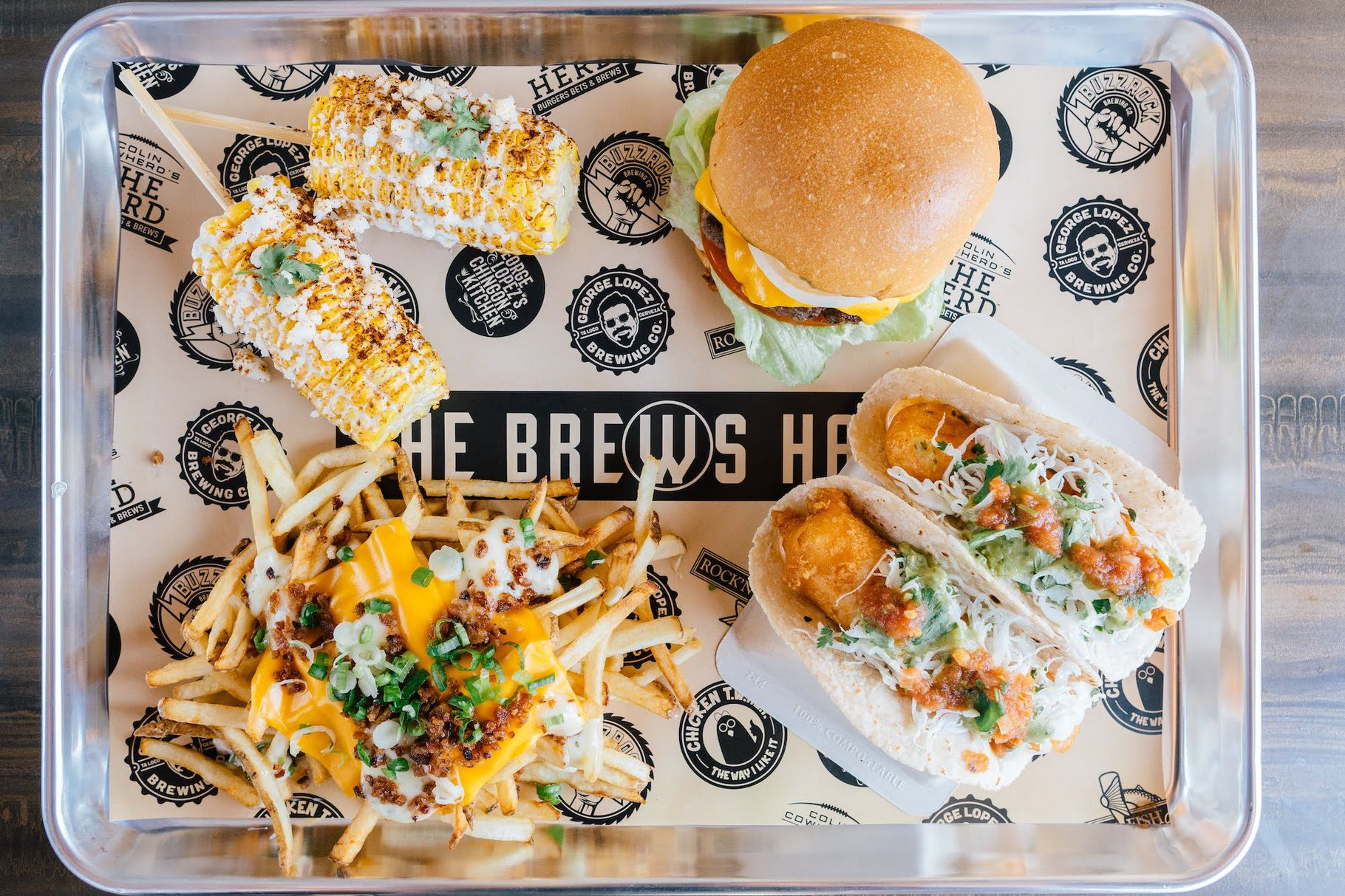 A variety of dishes, including a burger, elote, fries, and fish tacos, on a tray.